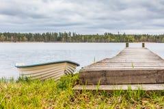 Barco de enfileiramento branco ao lado do cais de madeira foto de stock