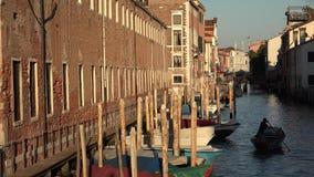Barco de enfileiramento do homem no canal de Veneza em Dawn Or Dusk fotografia de stock