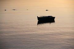 Barco de enfileiramento de madeira pequeno na superfície da água do mar do por do sol fotografia de stock