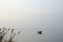 Barco de enfileiramento solitário na água calma Imagens de Stock Royalty Free