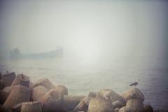 Barco de Fisher no mar nevoento em um amanhecer calmo Fotos de Stock Royalty Free