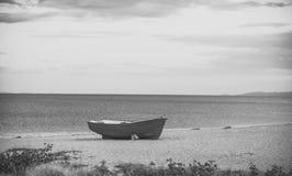 Barco de Fishermens no seacoast, na areia no dia nebuloso com o mar no fundo Barco de pesca na praia na noite Curso e Fotos de Stock Royalty Free