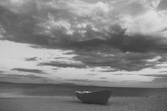 Barco de Fishermens no seacoast, na areia no por do sol com o mar do horisont no fundo Barco de pesca na praia na noite Curso Foto de Stock