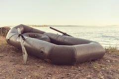 Barco de goma negro con los remos en la orilla imágenes de archivo libres de regalías