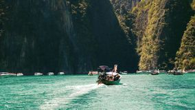 Barco de la cola larga que entra en laguna de la bahía del maya en un agua cristalina almacen de metraje de vídeo