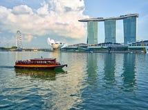 Barco de la excursión en Singapur contra la perspectiva de las atracciones principales Imagen de archivo libre de regalías