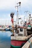 Barco de la pesca profesional en puerto con las redes y las banderas Imagen de archivo libre de regalías