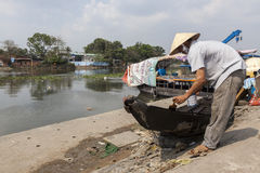 Barco de la pintura del hombre en el banco del río Mekong Foto de archivo