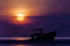 Barco de la ruina en la playa en la salida del sol Imagen de archivo libre de regalías