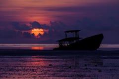 Barco de la ruina en la playa en la salida del sol Foto de archivo
