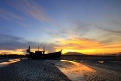 Barco de la silueta en la puesta del sol. Fotografía de archivo