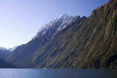 Barco de la travesía contra el paisaje de Milford Sound Foto de archivo libre de regalías