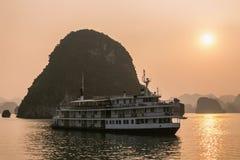 Barco de la travesía en la bahía de Halong de la puesta del sol Imagen de archivo