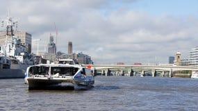 Barco de las podadoras del Támesis y autobuses rojos en el puente de Londres Foto de archivo libre de regalías