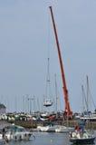 Barco de levantamento do guindaste no harbourside Imagem de Stock