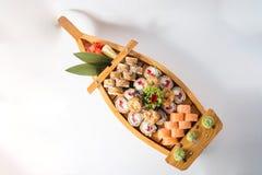 Barco de madeira com lotes do sushi com gengibre e wasabi fotografia de stock