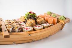 Barco de madeira com lotes do sushi com gengibre e wasabi fotos de stock royalty free