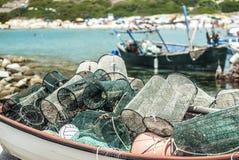 barco de madeira completamente de redes de pesca com uma praia, um mar azul e um fi Imagem de Stock Royalty Free