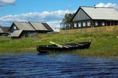 Barco de madeira no banco do lago na vila pequena Fotos de Stock