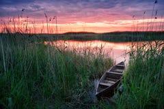 Barco de madeira no lago no por do sol Fotografia de Stock Royalty Free