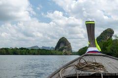 Barco de madeira tradicional contra o rio tropical com marco de Krabi Foto de Stock
