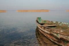 Barco de madeira velho na água clara fotografia de stock
