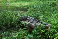 Barco de madeira velho na grama no banco do lago Imagens de Stock