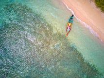barco de madeira Vermelho-amarelo-ciano no litoral tropical ensolarado fotografia de stock