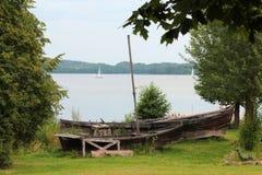 Barco de madera abandonado en la orilla del río en la tierra Foto de archivo