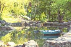 Barco de madera azul en la charca del parque en un día soleado Imagen de archivo libre de regalías