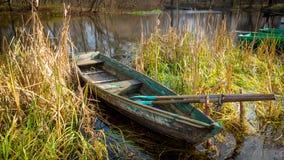 Barco de madera en cañas en el río fotografía de archivo libre de regalías