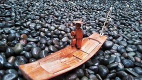 Barco de madera en el mar de rocas Foto de archivo libre de regalías