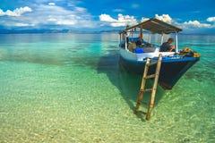 Barco de madera en las aguas claras del paraíso Foto de archivo