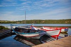 Barco de madera flotante del color con las paletas y su reflexión en a Imagen de archivo libre de regalías