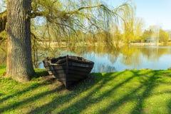 Barco de madera llevado viejo en tierra debajo de un árbol cerca de una pequeña charca con imagen de archivo libre de regalías
