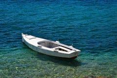 Barco de madera minúsculo en un mar Fotografía de archivo