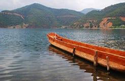 Barco de madera que flota en el lago Lugu Fotos de archivo