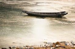 Barco de madera que flota en el mar contaminado Imagen de archivo