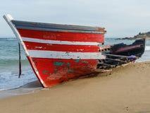 Barco de madera rojo abandonado en la playa Fotografía de archivo