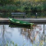 Barco de madera simple en el embarcadero de madera en la charca foto de archivo