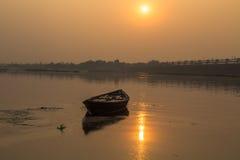 Barco de madera solitario en la puesta del sol en el agua del río Damodar Fotografía de archivo