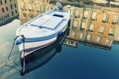 Barco de madera viejo, cielo e histórico antiguo y edificio con la reflexión en el agua azul Imagen de archivo libre de regalías