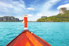 Barco de madera y una isla tropical en distancia Fotografía de archivo