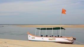 Barco de mar con una bandera roja en la orilla en el fondo de la bahía debajo del cielo azul metrajes