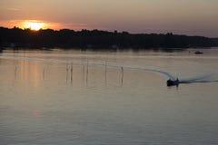 Barco de motor antes de la puesta del sol Foto de archivo libre de regalías