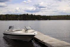 Barco de motor atado a un muelle de la cabaña en un lago del agua dulce Foto de archivo
