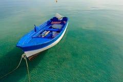 Barco de motor azul azul que flota en la agua de mar transparente tranquila en la isla de Kos del Griego Foto de archivo libre de regalías