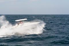 Barco de motor blanco que acomete a través de las ondas Imágenes de archivo libres de regalías
