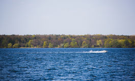 Barco de motor da velocidade no lago dos azuis celestes Foto de Stock