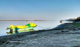 Barco de motor de madeira no banco de um rio Fotos de Stock Royalty Free
